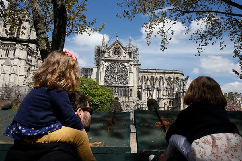 A family looks at Notre Dame Cathedral April 17, 2019, two days after a fire destroyed much of the church's wooden structure.