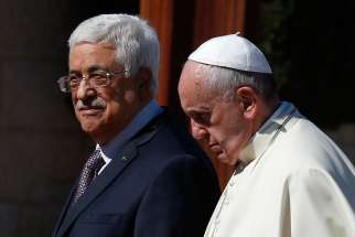Pope Francis walks with Palestinian President Mahmoud Abbas during an arrival ceremony at the presidential palace in Bethlehem, West Bank, May 25.