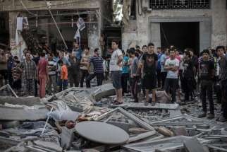 Palestinians look at a destroyed building in Gaza City shortly after an airstrike by Israeli Defense Forces July 17. Caritas Jerusalem officials say Gaza civilians are paying the price for the Israeli-Hamas conflict.