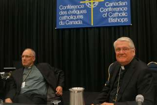 Bishop Douglas Crosby, right , spoke at a news conference Sept. 18 to wrap up the bishops' annual plenary.