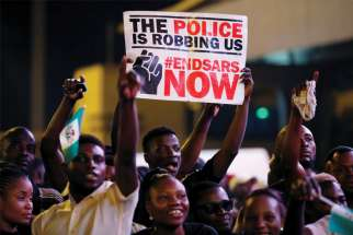 A demonstrator holds a sign during a protest in Lagos, Nigeria, Oct. 17 over alleged police brutality. Several Nigerian bishops have criticized police attacks that have left at least 12 protesters dead and hundreds injured. Emannuel Adegboyega, left, a Toronto high school student originally from Nigeria, implores Canadians to not take their freedom for granted.