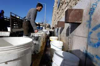 A man fills buckets with drinking water a a public filling area Feb. 3 in Aleppo, Syria. Access to clean drinking water is a basic human right and a key component in protecting human life, Pope Francis said Feb. 24.