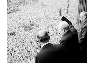 Winston Churchill waving to crowds in Whitehall on 8 May celebrating the end of the war.