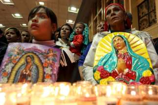 Pilgrims hold up images of Our Lady of Guadalupe during an annual pilgrimage in her honor at the cathedral in Ciudad Juarez, Mexico, Dec. 11.