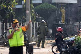 A member of the police bomb squad unit examines the site of a May 12 explosion outside Santa Maria Catholic Church in Surabaya, Indonesia. Christian leaders have called for unity following a spate of suicide bombings that targeted three churches, an apartment building and the police headquarters, the deadliest attacks in more than a decade.