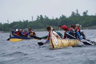 A couple of the crews engaged in a playful mini-race as the Canadian Canoe Pilgrimage got underway July 21 in Midland, Ont., the start of a 900 km journey.