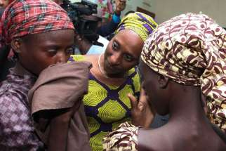 Oludolapo Osinbajo, wife of Nigerian Vice President Yemi Osinbajo, consoles one of the 21 released Chibok girls Oct. 13 in Abuja. Three Catholic leaders welcomed the release of some of the girls kidnapped in 2014 from a school in Chibok and urged the Nigerian government to prioritize the release of the remaining girls.
