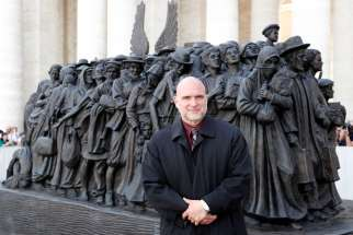Sculptor Timothy P. Schmalz poses with his statue after Pope Francis celebrated a Mass for the World Day of Migrants and Refugees in St. Peter's Square at the Vatican Sept. 29, 2019.