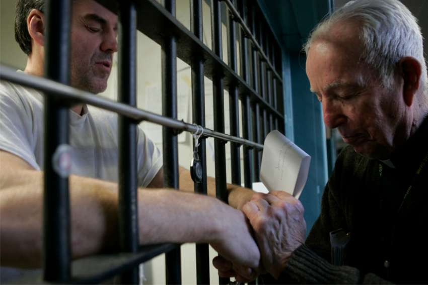 Father Tom McNally prays with death-row inmate Eric Wrinkles at Indiana State Prison in Michigan City in this Dec. 18, 2008, file photo. Wrinkles, who experienced a religious awakening in prison, was executed for triple-murderer Dec. 11, 2009. In Texas, a group of nearly 200 faith leaders, including 18 Catholics, signed a statement sent to the Texas Department of Criminal Justice July 23, 2019, asking the department to change its policy banning prison chaplains from execution chambers.