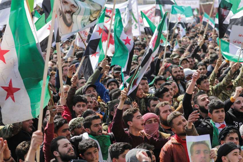 People carry banners and opposition flags during a demonstration marking the 10th anniversary of the start of the Syrian conflict, in the opposition-held city of Idlib, Syria, March 15. As Syria marks 10 years of devastating conflict, the country is in economic and social shambles with millions of people displaced and millions more living below the poverty line.