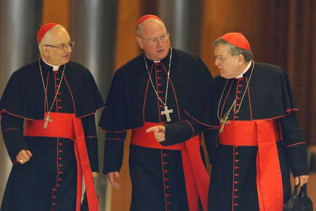 Cardinals Mauro Piacenza, prefect of the Congregation for Clergy, Timothy M. Dolan of New York, and Raymond L. Burke, prefect of the Supreme Court of the Apostolic Signature, talk as they walk through Paul VI hall before the morning session of the extrao rdinary Synod of Bishops on the family at the Vatican Oct. 16.