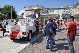 "People pose to take pictures with the popemobile in front of Gemelli Hospital in Rome June 27. Pope Francis will ride in a ""accessible"" popemobile that will not be bulletproof and will have a roof when he visits the Philippines from Jan. 15-19 next year."