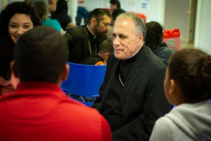 Cardinal Daniel N. DiNardo of Galveston-Houston, president of the U.S. Conference of Catholic Bishops, listens to immigrants recently released from U.S. custody July 1 at a Catholic Charities-run respite center in McAllen, Texas. A delegation of U.S. bishops traveled to the Diocese of Brownsville, Texas, to learn more about the detention of immigrants, mostly Central Americans, at the U.S.-Mexico border.