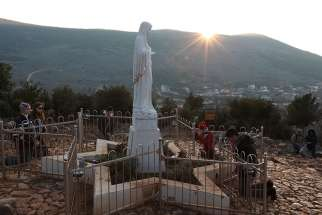 Pilgrims pray around a statue of Mary on Apparition Hill in Medjugorje, Bosnia-Herzegovina, in this Feb. 26, 2011, file photo.