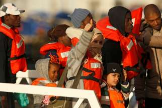 Migrants who were stranded on the nongovernmental organization migrant rescue ships Sea-Watch 3 and Professor Albrecht Penck disembark Jan. 9 from an Armed Forces of Malta patrol boat at its base in Valletta. Pope Francis issued a plea Jan. 6 to European governments to work together to find a way to assist the migrants.