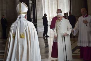 Retired Pope Benedict XVI prepares to greet Pope Francis during the opening of the Holy Door of St. Peter's Basilica at the Vatican in this Dec. 8, 2015, file photo.