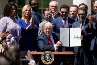 President Donald Trump holds up an executive order he signed during a White House ceremony May 3 to establish a faith-based office, the White House Faith and Opportunity Initiative.