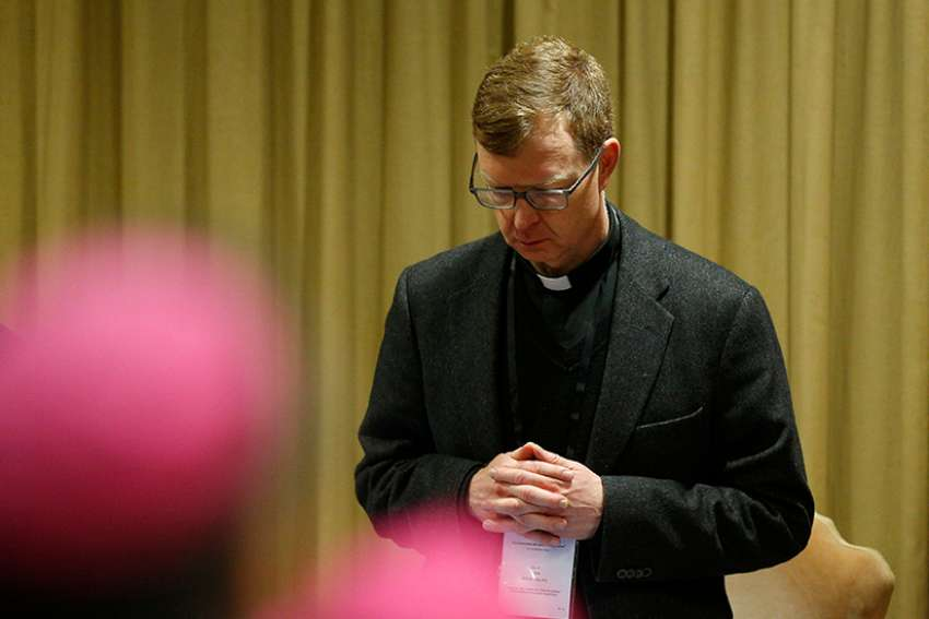 Jesuit Father Hans Zollner, president of the Centre for Child Protection at the Pontifical Gregorian University in Rome, prays at the start of the third day of the meeting on the protection of minors in the church at the Vatican Feb. 23, 2019.
