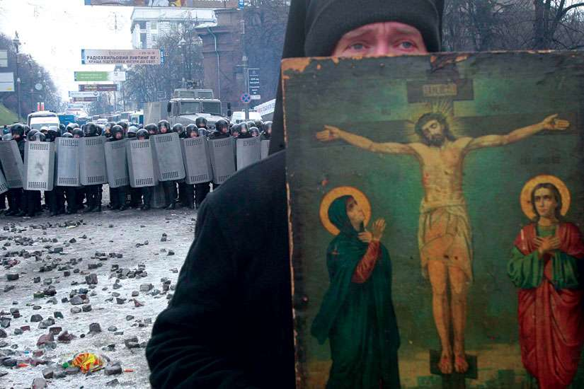 A clergyman holds a religious picture during a rally by pro-European Union protesters in Kiev, Ukraine. Ukrainians are finding it hard to understand why the world is paying so little attention to the conflict in Ukraine.