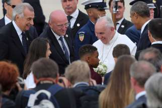Catholic school students greet Pope Francis with flowers after he arrived at Joint Base Andrews in Maryland Sept. 22.