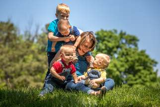 A mother plays with her triplets and other son at a park in St. Louis April 24.