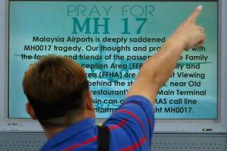 "A bystander points in front of a ""Pray for MH17"" message on a flight information board at Malaysia's Kuala Lumpur International Airport July 18.  Catholics involved in the fight against HIV and AIDS took a few moments July 21 to remember their friends and colleagues who perished in the Malaysia Airlines flight shot down over eastern Ukraine."