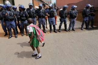School children walk past a line of police officers during protests against the cost of higher education in Johannesburg, South Africa, Oct. 12. After chaos broke out in a Catholic church as it hosted a meeting to resolve a university crisis, South Africa's Jesuits said the church would no longer be open for these talks.
