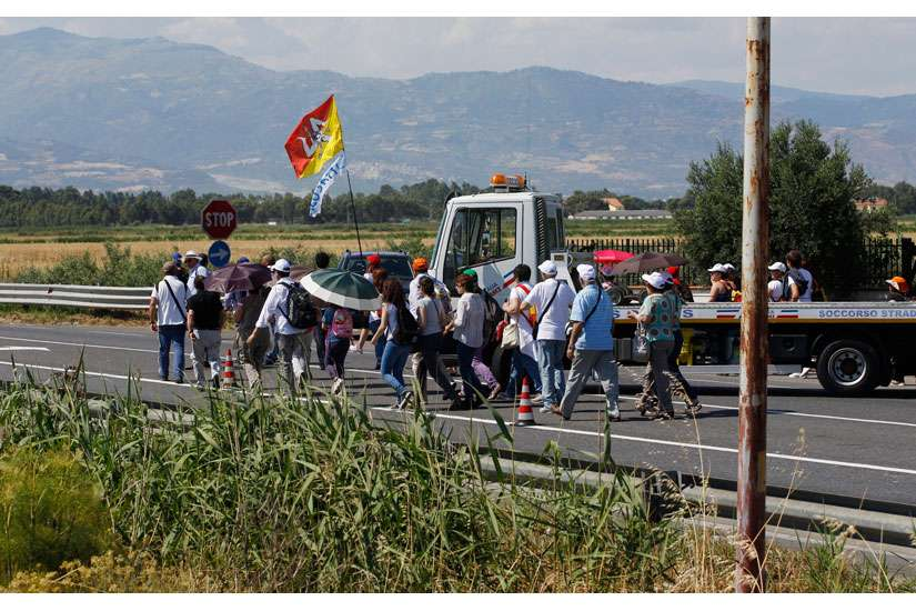"People walk on a highway as they arrive for Pope Francis' Mass attended by 250,000 people in Sibari, in Italy's region, June 21. During his homily, the pope said ""mafiosi"" are not in communion with God and are excommunicated. The Calabria region is home of the 'Ndrangheta crime organization, known for drug trafficking."