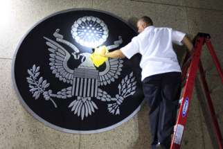 A worker cleans the seal of the United States of America after it was placed on the wall at the main entrance of the U.S. Embassy in Havana Aug. 14. U.S. Secretary of State John Kerry officially reopened the U.S. Embassy in Cuba.