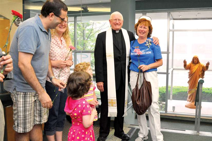 Fr. Michael Prieur shares some smiles with a family.