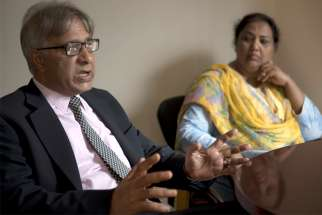 Peter Jacob, executive director of the Center for Social Justice based in Lahore, Pakistan, gestures during an interview with a Catholic News Service reporter in Washington July 18, 2019. Looking on is Rubina Feroze Bhatti of Pakistan, a founding member and current general secretary of Taangh Wasaib Organization, a rights-based development group.
