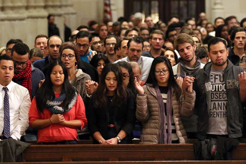 People recite the Lord's Prayer during a Mass for young adults Dec. 7 at St. Patrick's Cathedral in New York City.