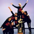 Seven of the nine members of St. Marcellinus' improvisational team strike a pose with the trophy they brought home after winning the national championships in March.