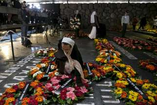 "A nun lays a wreath beside the name of a former concentration camp during a ceremony titled ""Unto Every Person There is a Name"" at Yad Vashem Holocaust memorial in Jerusalem April 16, 2015. That day, Israel marked its annual Holocaust Remembrance Day, commemorating the 6 million Jews killed by the Nazis during World War II."