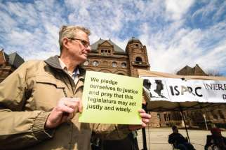 At an ISARC prayer vigil in front of the Ontario Legislature before the 2017 budget was passed, Robin Wardlaw holds a sign asking for a budget that favours the poor.