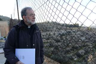 Bishop Lionel Gendron of Saint-Jean-Longueuil, Quebec, looks through a fence at the Cremisan Valley from the Salesian Sisters' convent in Beit Jalla, West Bank 2015.