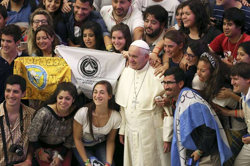 Pope Francis poses for a photo with Argentine youths during his weekly audience in Paul VI hall at the Vatican Aug. 19.
