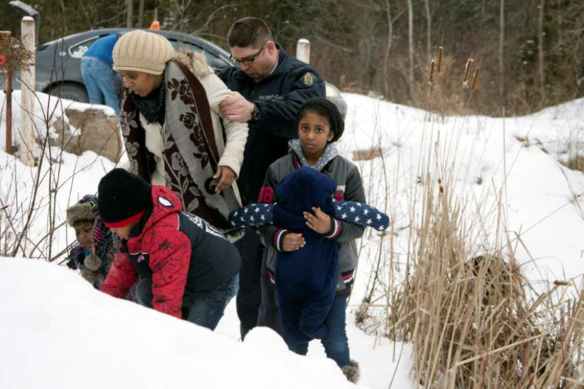 A woman who told police that she and her family were from Sudan is taken into custody by a Royal Canadian Mounted Police officer after arriving by taxi and walking across the U.S.-Canada border into Quebec.
