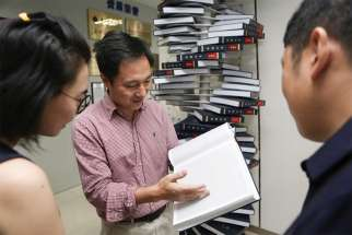 "Scientist He Jiankui shows ""The Human Genome,"" a book he edited, at his company. Direct Genomics, in Shenzhen, China, Aug.4, 2016. An ethicist calls Jiankui's gene editing on a human embryo ""a train wreck of a thing to do."""