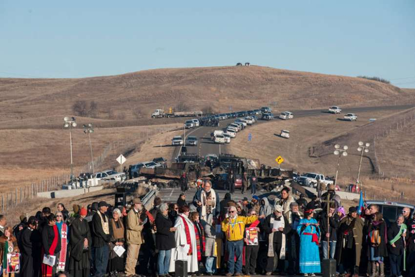 Clergy of many faiths from across the United States participate in a prayer circle Nov. 3 in front of a bridge in Standing Rock, N.D., where demonstrators confront police during a protest of the Dakota Access pipeline. Demonstrations against the pipeline are taking place on the Standing Rock Indian Reservation near Cannonball, N.D.