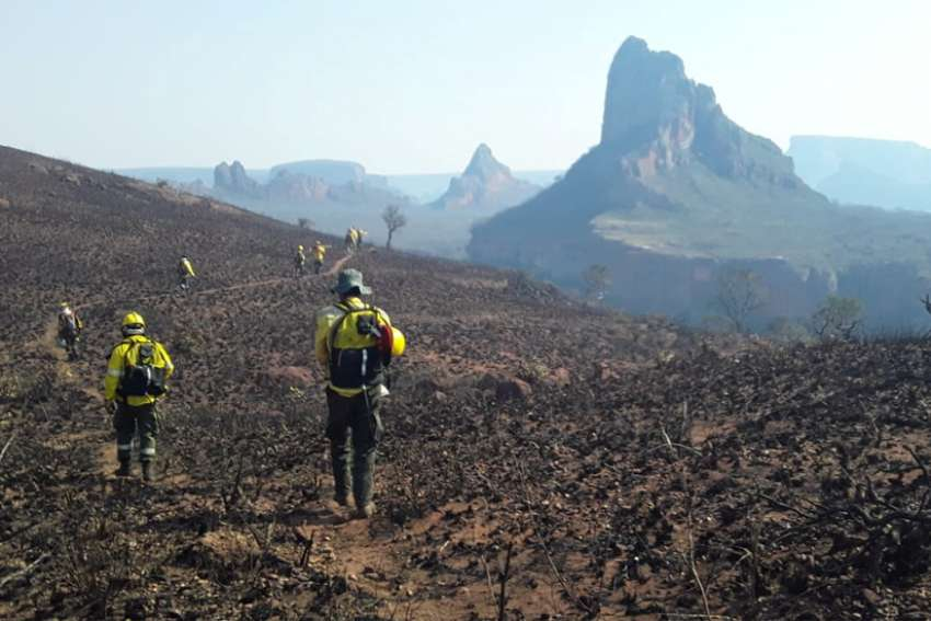 Firefighters near Robore, Bolivia, walk where wildfires have destroyed the forest Aug. 19, 2019.