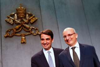 Jean-Baptise de Franssu, the new president of the Vatican bank, and outgoing president Ernst Von Freyberg pose during a news conference at the Vatican July 9.