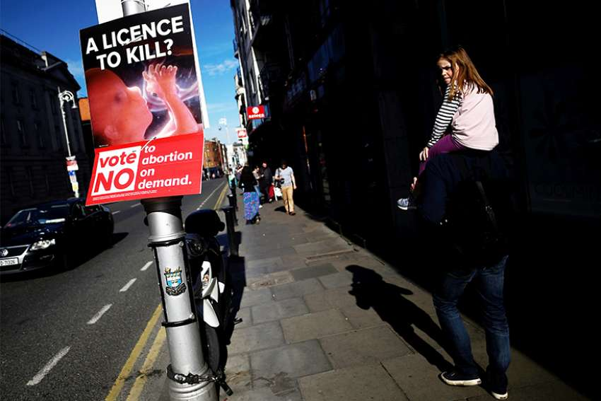 People walk past a pro-life poster in Dublin May 7. Ireland votes May 25 on whether the right to life of the unborn should continue to be enshrined in the constitution.