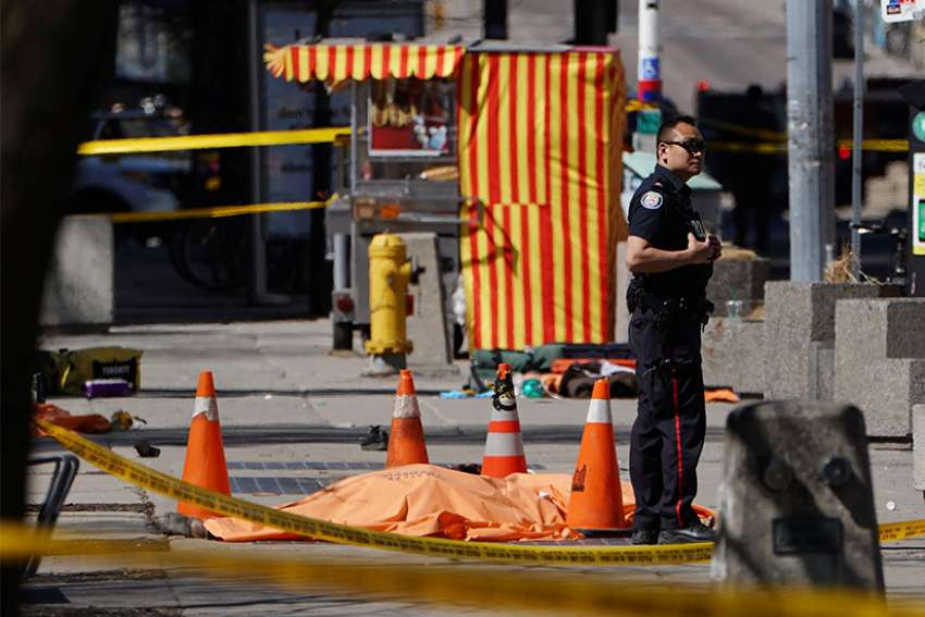 A police officer stands next to a victim at the site where a van struck multiple people at a major intersection in Toronto's northern suburbs April 23. At least 10 people were dead and 15 were injured, authorities said.