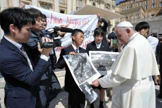 Pope Francis examines photos of the 1945 atomic bombing of Japan as he greets members of the Hiroshima and Nagasaki Youth Peace Messengers this past June.