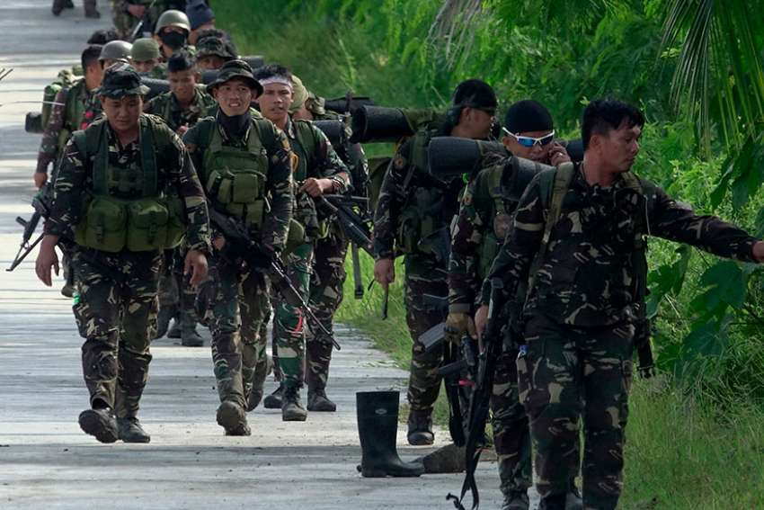 Government forces of the Philippines patrol a street in Pigcawayan June 22.