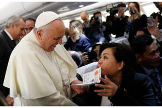 Pope Francis accepts a card from Filipino reporter Lynda Jumilla Abalos of ABSCBN television while greeting media aboard the papal flight to Colombo, Sri Lanka, Jan. 12. The card was made by the children of the journalist to welcome the pope to the Philippines.