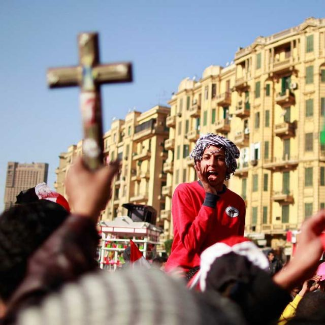 A demonstrator holds up a crucifix and a Quran during a protest at Tahrir square in Cairo. Religious communities can help pro-democracy movements in the Middle East and North Africa by upholding human dignity, says a Vatican official.