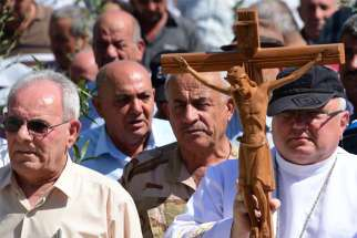 Father Andrzej Halemba is seen in a 2017 file photo carrying a crucifix during a procession of the Christians in Qaraqosh, Iraq.