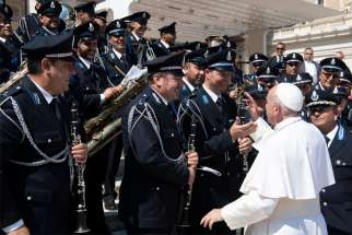 Pope Francis greets band members during an audience with members of the Italian Prison Police in St. Peter's Square at the Vatican Sept. 14, 2019. The pope told prison guards, chaplains and officials that life sentences in prison without the possibility of parole are not the solution but a problem to be solved.